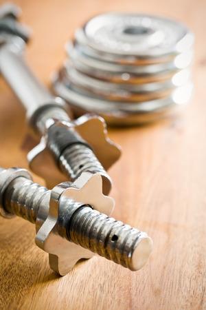 kilos: chrome dumbbell on wooden floor Stock Photo