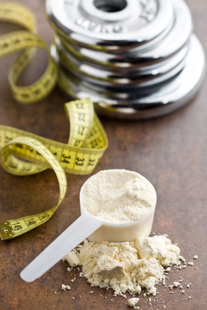 strength training: the whey protein in scoop and dumbbell Stock Photo