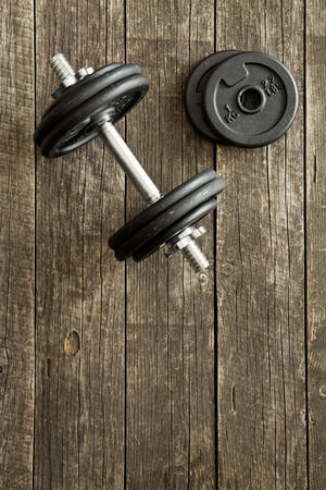 kilos: iron dumbbell on old wooden background Stock Photo
