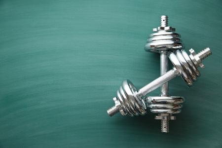 dumbbell: iron dumbbell on green chalkboard Stock Photo