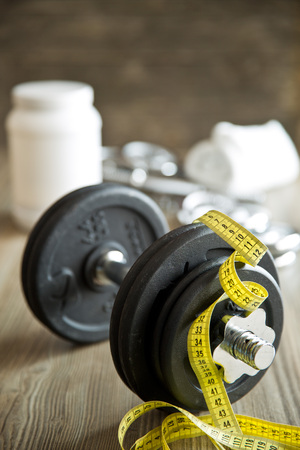 kilos: measuring tape and iron dumbbell on wooden floor