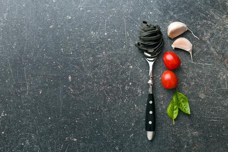 cocina antigua: fideos, ajo, tomate y albahaca sobre la mesa de la cocina antigua Foto de archivo