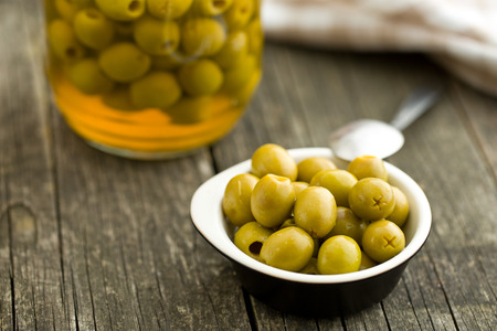 pitted: pitted green olives in bowl on wooden table Stock Photo