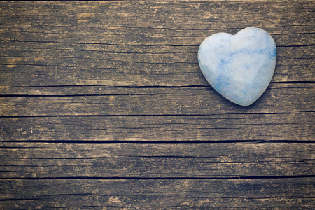 heart of stone: stone heart on old wooden background