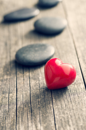 hardness: red stone heart on old wooden background Stock Photo