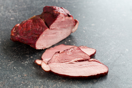 smoked: sliced smoked pork meat on kitchen table Stock Photo
