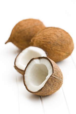 halved: halved and whole coconut on white table Stock Photo