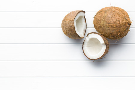 halved and whole coconut on white table Banco de Imagens