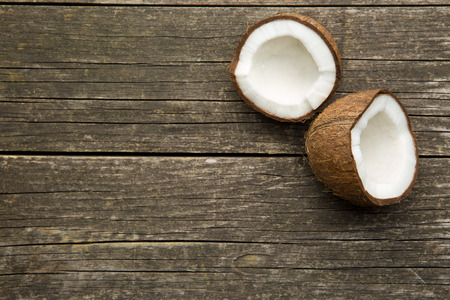 the halved coconut on old wooden background
