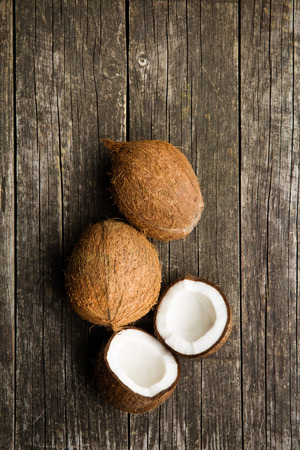 halved and whole coconut on old wooden background