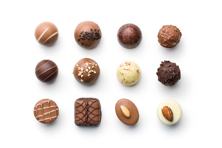 top view of various chocolate pralines on white background Foto de archivo