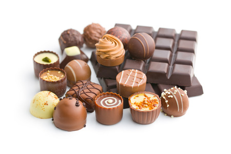 various chocolate pralines and chocolate bar on white background Imagens