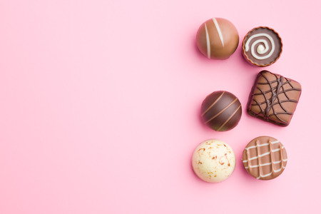 chocolate pralines on pink background