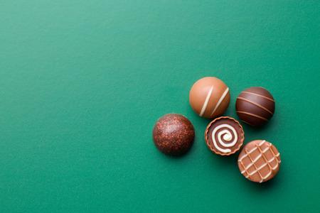 chocolate pralines on a green chalkboard