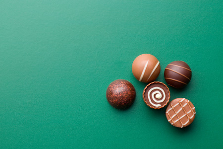chocolate pralines on a green chalkboard