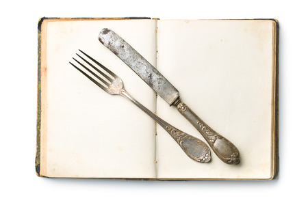 kulinarne: vintage book and cutlery on white background