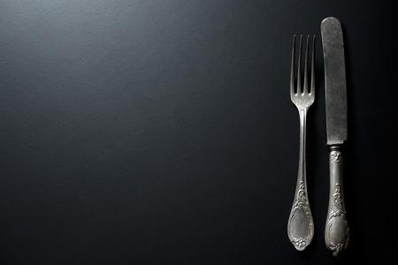 restaurant dining: old vintage knife and fork on black background