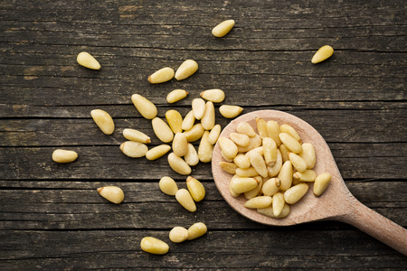 pine nuts: pine nuts on a wooden spoon