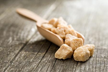unrefined: unrefined cane sugar in wooden scoop Stock Photo