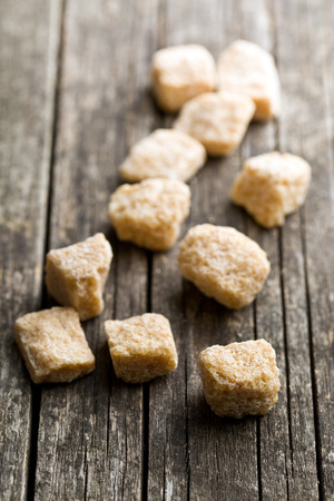 unrefined: unrefined cane sugar cubes on old wooden table