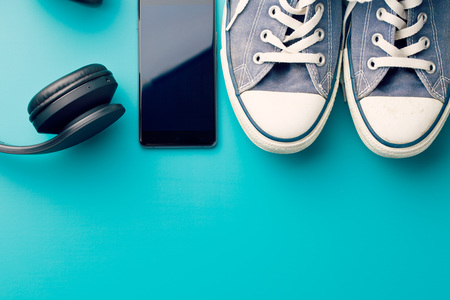 colorful background: headphones, smart phone and sneakers on colorful background