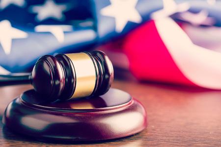 justicia: el juez martillo y de fondo con la bandera de EE.UU. Foto de archivo