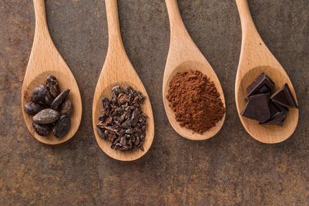 Il cacao e il cioccolato fondente in cucchiai di legno Archivio Fotografico - 55312337