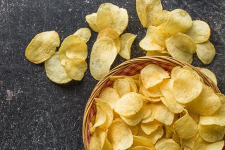 Chrupiące chipsy ziemniaczane w misce z wikliny na starym stole w kuchni