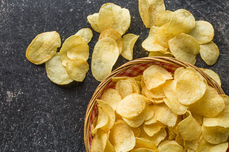 crunchy: Crispy potato chips in a wicker bowl on old kitchen table Stock Photo