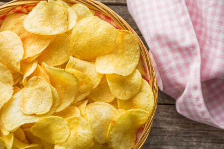 Crispy potato chips in a wicker bowl on old kitchen table Stockfoto