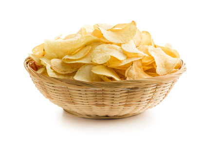 Crispy potato chips in a wicker bowl on white background Фото со стока