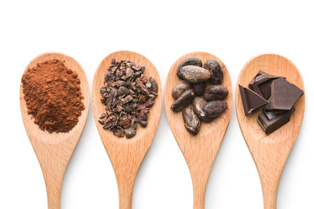 cocoa and dark chocolate in wooden spoons on white background Stockfoto