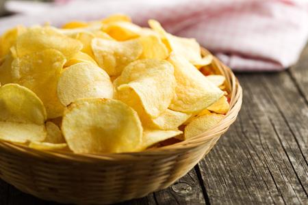 Crispy potato chips in a wicker bowl on old kitchen table Archivio Fotografico