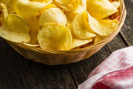 crispy: Crispy potato chips in a wicker bowl on old kitchen table Stock Photo