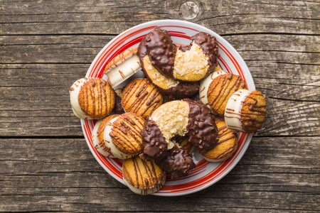 biscuits: Sweet dessert. Biscuits with chocolate icing on old wooden table. Stock Photo