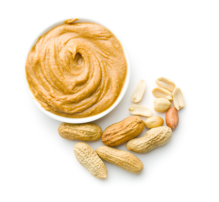 butter: Creamy peanut butter and peanuts  isolated on white background. Spreads peanut butter in the bowl. Stock Photo