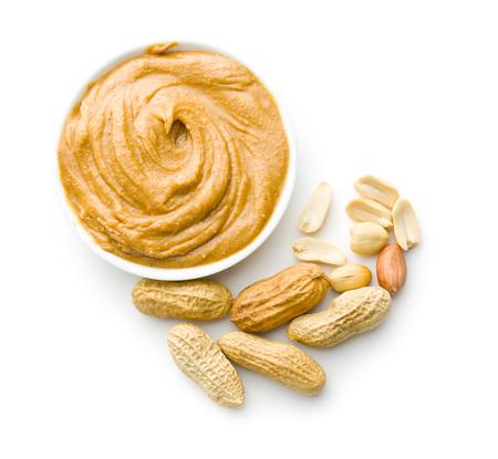mantequilla de maní cremosa y cacahuetes aislados sobre fondo blanco. Los diferenciales de mantequilla de maní en el recipiente.