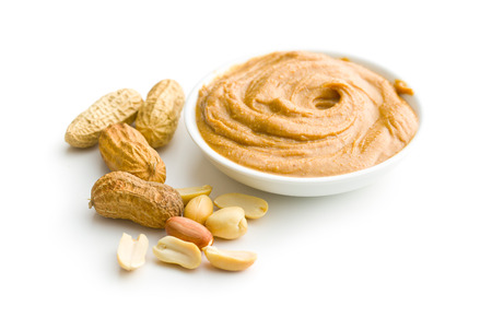allergic ingredients: Creamy peanut butter and peanuts  isolated on white background. Spreads peanut butter in the bowl. Stock Photo