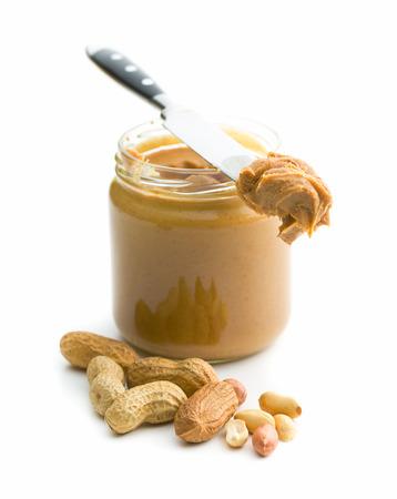 Romige pindakaas en pinda's op een witte achtergrond. Spreads pindakaas in de pot. Stockfoto