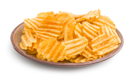 crinkle: Crinkle cut potato chips isolated on white background. Tasty spicy potato chips on plate.
