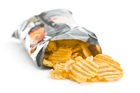 Crinkle cut potato chips isolated on white background. Potato chips poured out from packing.