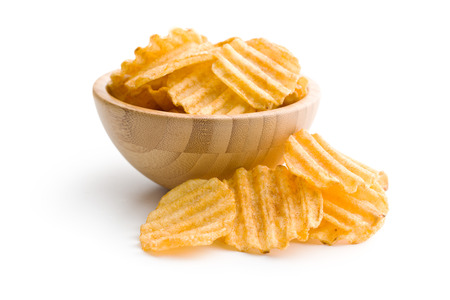 Crinkle cut potato chips isolated on white background. Tasty spicy potato chips in bowl.