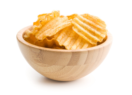 crinkle: Crinkle cut potato chips isolated on white background. Tasty spicy potato chips in bowl.