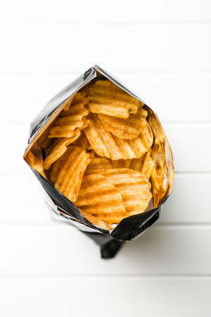 crinkle: Crinkle cut potato chips on white table. Tasty spicy potato chips in bag. Top view.