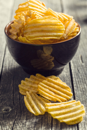 crinkle: Crinkle cut potato chips on kitchen table. Tasty spicy potato chips in bowl.
