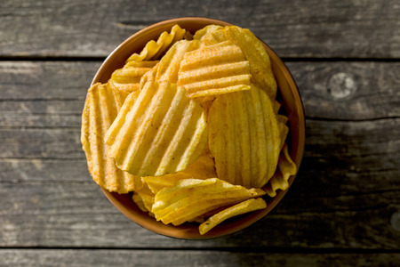 crinkle: Crinkle cut potato chips on kitchen table. Tasty spicy potato chips in bowl. Top view.