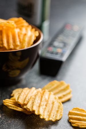 crinkle: Crinkle cut potato chips on table. Tasty spicy potato chips and tv remote controller.