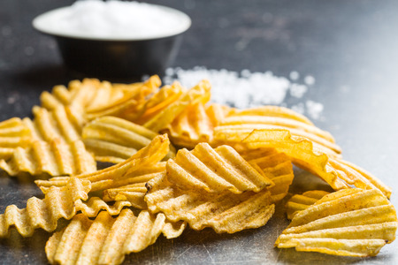ruffle: Crinkle cut potato chips on kitchen table. Tasty spicy potato chips with salt. Stock Photo