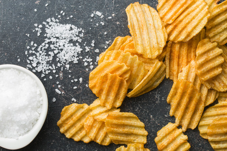 crinkle: Crinkle cut potato chips on kitchen table. Tasty spicy potato chips with salt.Top view.