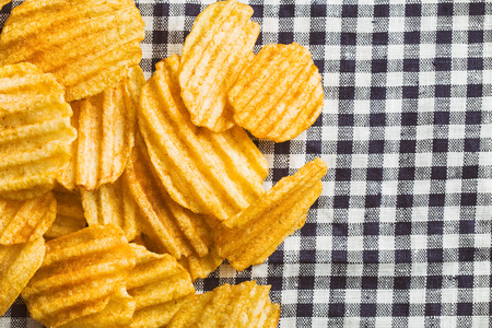 crinkle: Crinkle cut potato chips on checkered tablecloth. Tasty spicy potato chips.